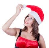 有圣诞老人帽子接触的微笑的美丽的女孩 库存图片