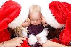 有圣诞老人帽子的两名妇女亲吻婴孩的 图库摄影