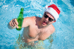 有圣诞老人帽子的人在手中集会在与啤酒瓶的游泳池的 库存照片
