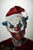 有圣诞老人帽子的可怕邪恶的小丑 免版税图库摄影