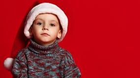 有圣诞老人帽子的圣诞节定期的男孩 库存照片