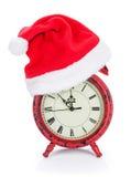 有圣诞老人帽子的圣诞节时钟 免版税库存图片