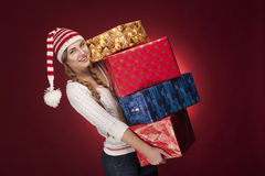 有圣诞老人帽子的妇女与存在 库存图片