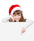 有圣诞老人帽子的愉快的圣诞节女孩指向得下来 隔绝在whi 免版税图库摄影