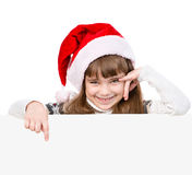 有圣诞老人帽子的愉快的圣诞节女孩指向得下来 隔绝在whi 库存图片