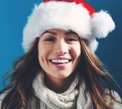 有圣诞老人帽子的愉快的少妇 免版税图库摄影