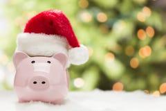 有圣诞老人帽子的桃红色存钱罐在雪花 免版税图库摄影