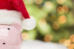 有圣诞老人帽子的桃红色存钱罐在雪花 免版税库存图片