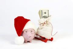 有圣诞老人帽子的桃红色站立在有圣诞老人的红色雪撬旁边的存钱罐和玻璃请求和堆金钱美国人一百美元b 免版税库存图片