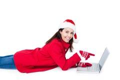 有圣诞老人帽子的浅黑肤色的男人说谎在地板上指向她的膝上型计算机的 免版税库存图片