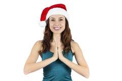 有圣诞老人帽子的瑜伽妇女在namaste姿势 免版税库存照片