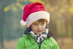 有圣诞老人帽子的男孩在公园 免版税库存照片