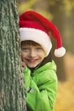 有圣诞老人帽子的男孩在公园 图库摄影