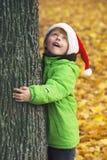 有圣诞老人帽子的男孩在公园 免版税图库摄影