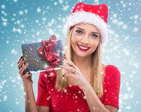 有圣诞老人帽子的美丽的妇女,拿着两红色礼物盒-降雪 库存照片