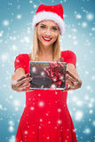 有圣诞老人帽子的美丽的妇女,拿着两红色礼物盒-降雪 免版税库存图片