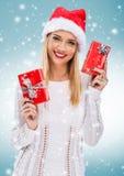 有圣诞老人帽子的美丽的妇女,拿着两红色礼物盒-降雪 图库摄影