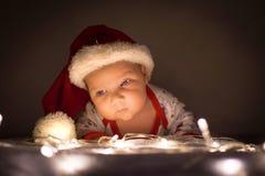 有圣诞老人帽子的逗人喜爱的新出生的婴孩抬了他的在光的头在圣诞树下 库存图片
