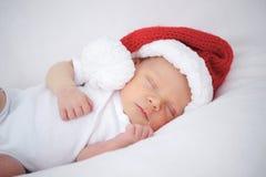 有圣诞老人帽子的逗人喜爱的新出生的婴孩 库存照片