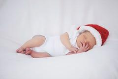 有圣诞老人帽子的逗人喜爱的新出生的婴孩 免版税库存图片