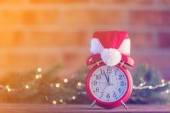 有圣诞老人帽子的闹钟有圣诞节神仙的Ligths 免版税图库摄影