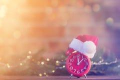有圣诞老人帽子的闹钟有圣诞节神仙的Ligths 库存图片