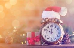 有圣诞老人帽子的闹钟有圣诞节神仙的Ligths 库存照片