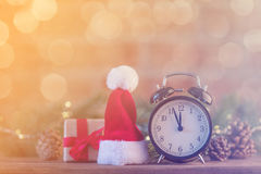 有圣诞老人帽子的闹钟有圣诞节神仙的Ligths 免版税库存照片