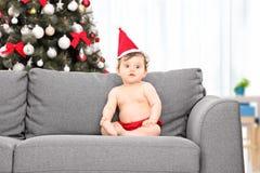 有圣诞老人帽子的婴孩和在她后的圣诞树 免版税图库摄影