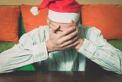 有圣诞老人帽子盖子的年轻人他的面孔用感到他的手偏僻和哀伤在新年和圣诞节假日消沉 免版税库存照片