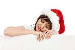 有圣诞老人帽子睡觉的少妇 库存照片