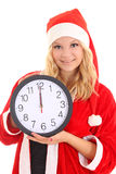 有圣诞老人帽子藏品时钟的女孩 免版税图库摄影
