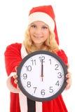 有圣诞老人帽子藏品时钟的女孩 免版税库存图片