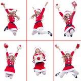 有圣诞老人服装跳跃的愉快的女孩 图库摄影