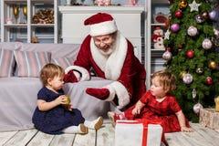 有圣诞老人的两个小女孩在有圣诞节装饰的演播室 库存图片