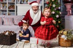 有圣诞老人的两个小女孩在有圣诞节装饰的演播室 图库摄影