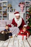 有圣诞老人的两个小女孩在有圣诞节装饰的演播室 免版税图库摄影