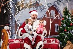 有圣诞老人的两个小女孩在有圣诞节装饰的演播室 库存照片