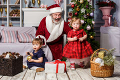 有圣诞老人的两个小女孩在有圣诞节装饰的演播室 免版税库存照片