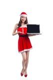 有圣诞老人的亚裔圣诞节女孩给举行膝上型计算机iso穿衣 库存图片