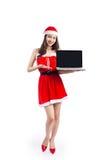 有圣诞老人的亚裔圣诞节女孩给举行膝上型计算机iso穿衣 库存照片