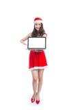 有圣诞老人的亚裔圣诞节女孩给举行膝上型计算机iso穿衣 免版税库存照片