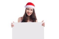 有圣诞老人的亚裔圣诞节女孩给拿着空白的标志穿衣 免版税库存照片