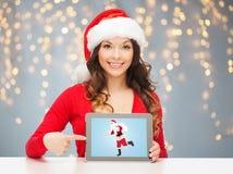 有圣诞老人的妇女在片剂个人计算机屏幕上 库存图片