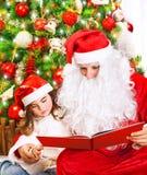 有圣诞老人的小女孩读了书 免版税库存图片