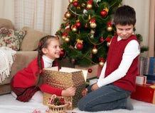 有圣诞老人的帽子的孩子乐趣和使用,在家分享礼物,圣诞节装饰,愉快的情感,寒假概念 免版税库存图片