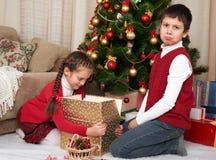 有圣诞老人的帽子的孩子乐趣和使用,在家分享礼物,圣诞节装饰,愉快的情感,寒假概念 库存图片