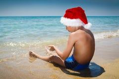 有圣诞老人的帽子的滑稽的小男孩坐海滩 库存照片