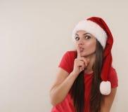 有圣诞老人的帽子的滑稽的少妇从您的一个秘密Chri的 免版税库存图片