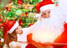 有圣诞老人的逗人喜爱的小女孩 库存图片